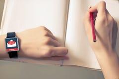 En mejl direktanslutet på en smart klocka En smart klocka på en hand för kvinna` s Meddelandeonline-symbol Arkivfoton