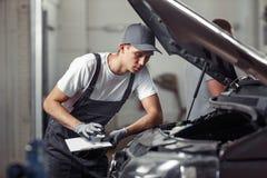 En mekaniker fixar en bil på en bilservice royaltyfri foto