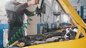 En mekaniker kontrollerar det elektriskt i huven av bil- reparera i motorrum arkivbilder
