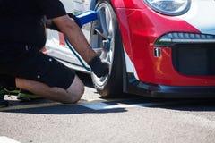 En mekaniker kontrollerar hjulet av en supercar för start loppet arkivbild