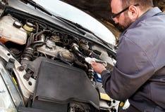 En mekaniker kontrollerar oljan på en bil som repareras arkivbild