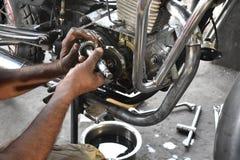 En mekaniker som reparerar motorcykeln, underhåll som är tekniskt royaltyfria foton