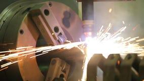 En mekanisk maskin som klipper stycken av metallröret arkivfilmer