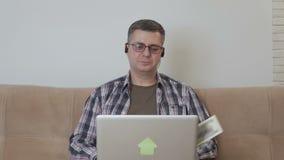 En mellersta åldrig man som sitter på en soffa med en bärbar dator Dollar är fallande pengar lager videofilmer