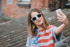 En mest hippest flicka i en gammal borggård med en telefon gör en selfie Fotografering för Bildbyråer