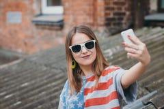 En mest hippest flicka i en gammal borggård med en telefon gör en selfie Royaltyfri Bild