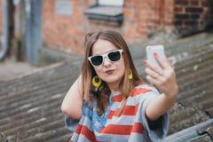 En mest hippest flicka i en gammal borggård med en telefon gör en selfie Arkivbild