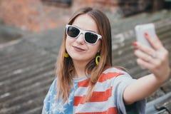 En mest hippest flicka i en gammal borggård med en telefon gör en selfie Royaltyfri Foto