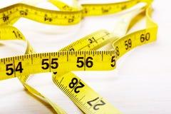 En mesurant la bande sur la table en bois, fermez-vous  Photo libre de droits