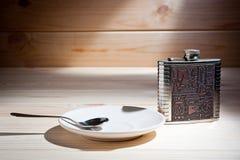 En metallflaska och ett tefat med en tesked på en träyttersida arkivbild