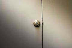 En metallisk knopp på den vita dörren arkivbilder