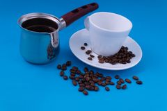 En metallkruka av nytt bryggade kaffeställningar bredvid vit disk och travde kaffebönor arkivbild