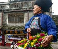En Miao kvinna som säljer blommor på Fenghuang den forntida staden i Hunan, Kina Royaltyfri Fotografi