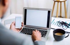 En midsection av affärsmannen med smartphonen och bärbara datorn som sitter på tabellen som arbetar fotografering för bildbyråer