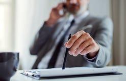 En midsection av affärsmannen med smartphonen som sitter på tabellen som gör en påringning fotografering för bildbyråer