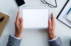 En midsection av affärsmannen som sitter på tabellen, genom att använda minnestavlan En bästa sikt kopiera avstånd arkivbilder