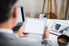 En midsection av affärsmannen som sitter på tabellen, genom att använda minnestavlan En bakre sikt kopiera avstånd royaltyfri fotografi