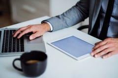 En midsection av affärsmannen som sitter på tabellen, genom att använda minnestavlan kopiera avstånd arkivbilder