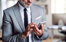 En midsection av affärsmannen som står i ett kontor, genom att använda smartphonen arkivbild