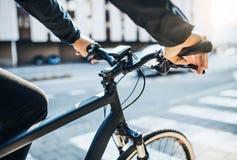 En midsection av affärsmanpendlaren med den elektriska cykeln som reser för att arbeta i stad arkivfoton