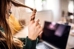 En midsection av den unga kvinnliga studenten som sitter p? tabellen, genom att anv?nda b?rbara datorn fotografering för bildbyråer