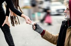 En midsection av kvinnan som ger pengar till den hemlösa tiggaremannen som sitter i stad arkivbild
