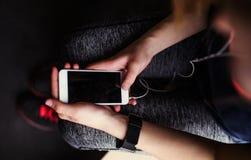 En midsection av unga flickan eller kvinnan med hörlurar och smartphonen i en idrottshall fotografering för bildbyråer