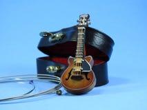 En miniatyrelektrisk gitarr, dess svarta fall och några rader arkivfoto