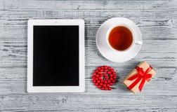 En minnestavla, en kopp te, en gåvaask och röda pärlor på en grå bakgrund Top beskådar Arkivbild