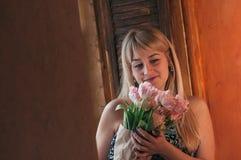 En mjuk fokusbild av kvinnan med blommor vid fönstret arkivfoton