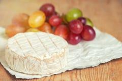 En mjuk mognad camembertost och druvor på ett träbräde arkivbilder