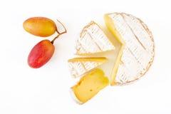 En mjuk mognad camembertost och några druvor som isoleras på vit bakgrund Top beskådar arkivfoto