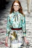 En modell går landningsbanan under den Gucci showen arkivfoto