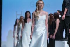 En modell går landningsbanan under 14th expobröllop för modeshowen Arkivfoton