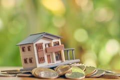 En modellhusmodell förläggas på en hög av mynt använda som bakgrundsaffärsidé och fastighetbegrepp med kopieringsutrymme royaltyfria bilder