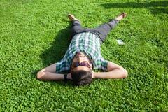 En modemitt - den östliga mannen med skägget, modehårstil vilar på härlig dagtid för grönt gräs Royaltyfri Foto
