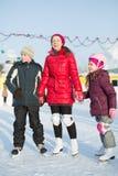 En moder med barn som står på den utomhus- åka skridskor isbanan Royaltyfri Bild