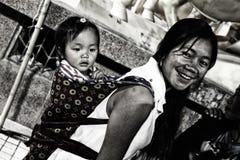 En moder med en behandla som ett barn på henne tillbaka , cangyuan, Kina Arkivbild