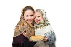En moder med hennes dotter bär rysssjaletthåll en platta av pannkakor Arkivbild