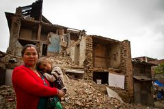 En moder och ett barn utanför en jordskalv fördärvade huset i Bhaktap Arkivbild