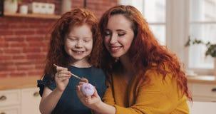 En moder och hennes ägg för dottermålningpåsk i hemtrevligt kök De som skrattar och, har roligt Lycklig familj som förbereder sig lager videofilmer