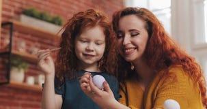 En moder och hennes ägg för dottermålningpåsk i hemtrevligt kök De som skrattar och, har roligt Lycklig familj som förbereder sig stock video