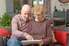 En moder och hennes vuxna son som ser en digital minnestavla arkivbilder