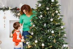 En moder och en son som dekorerar päls-trädet Royaltyfri Fotografi