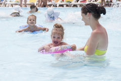 En moder och två döttrar simmar i en offentlig pöl royaltyfri bild