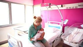 En moder ser hennes nyfött behandla som ett barn i sjukhuset lager videofilmer