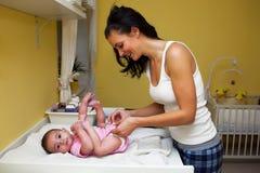 En moder som ändrar henne, behandla som ett barn nappyen. Royaltyfri Foto
