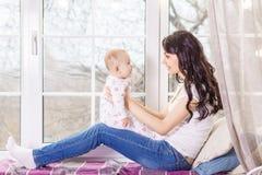 En moder som ammar hennes litet, behandla som ett barn flickan i henne armar Arkivfoto