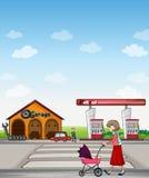 En moder som promenerar en garage- och bensinstation Fotografering för Bildbyråer