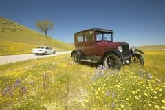 En modern bilkörning förbi en rödbrun modell T parkerade tillsammans med en scenisk väg som omgavs av vårblommor, rutt 58, Shell  Arkivfoto